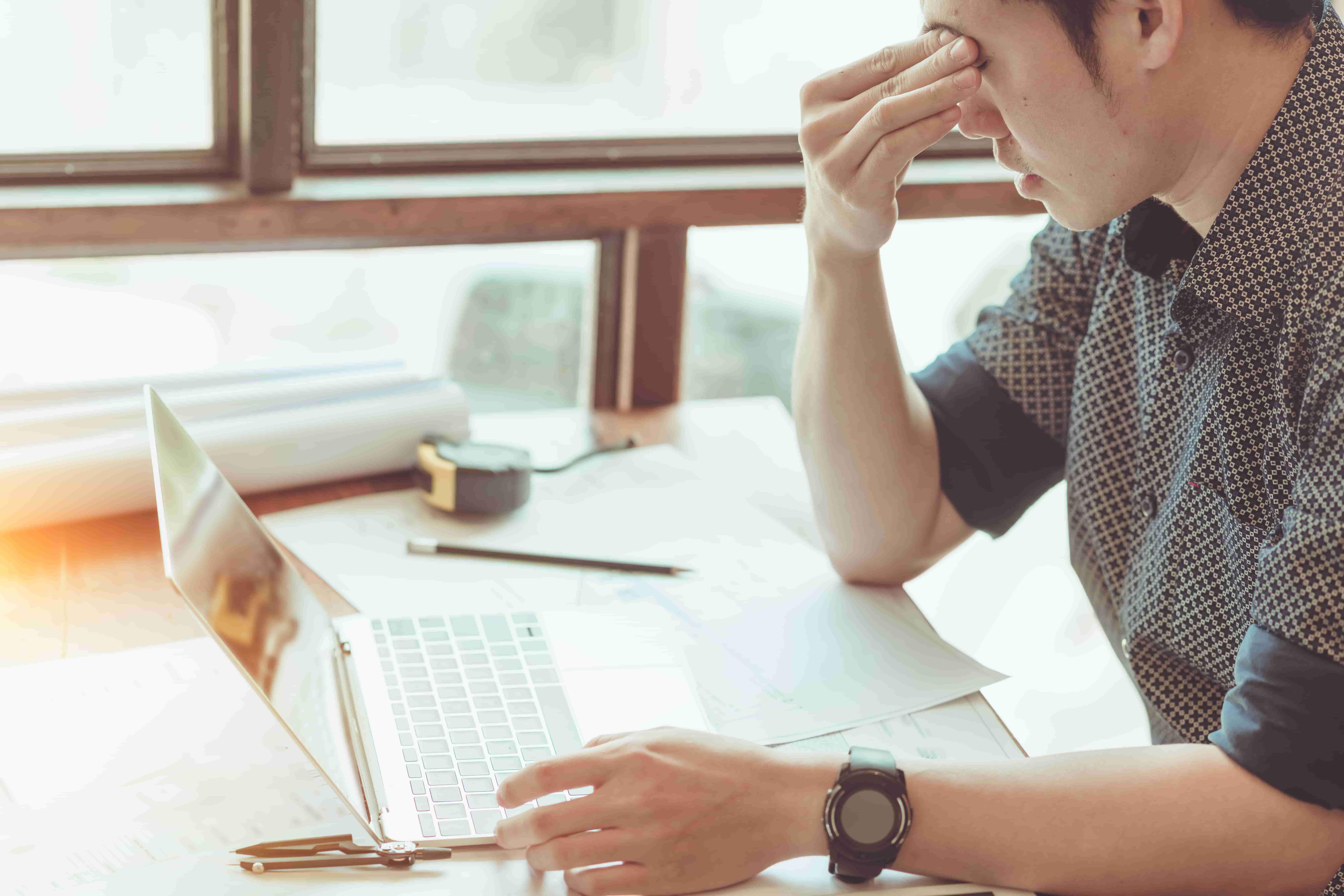 Homme assis à un bureau devant ordinateur n'arrivant plus à se concentrer