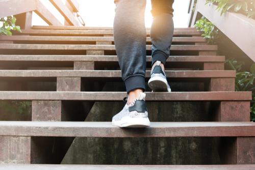 Homme en baskets montant des escaliers avec le soleil derrière