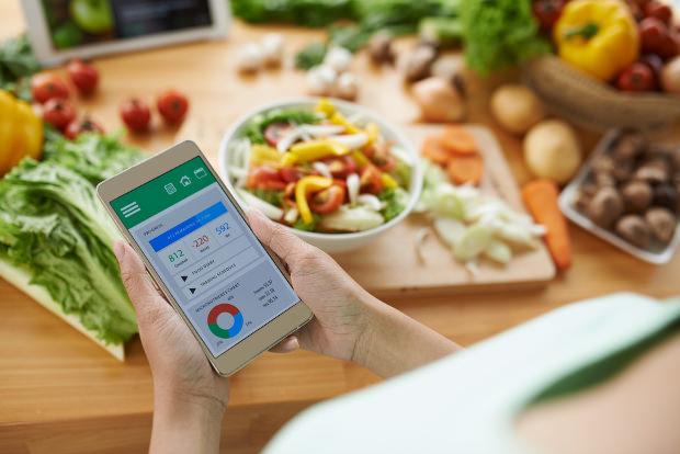 Photo montrant une nourriture équilibrée et une femme utilisant une application santé sur son smartphone