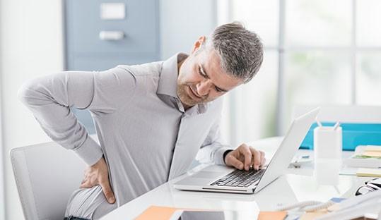 Salarié assis à son poste souffrant d'un mal de dos