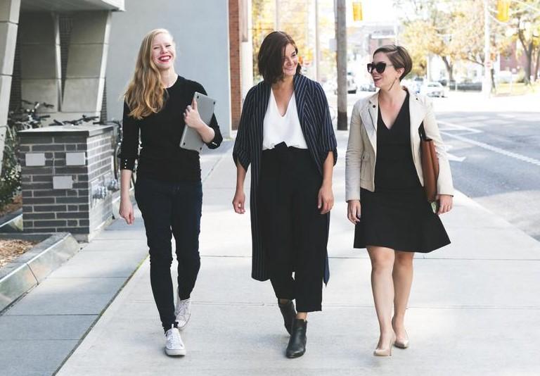 trois-salariees-en-tenue-de-bureau-marchant-en-ville-tout-en-discutant